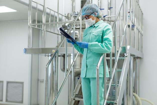 Cuadro de la planta, científico de pie en las escaleras de acero con tableta