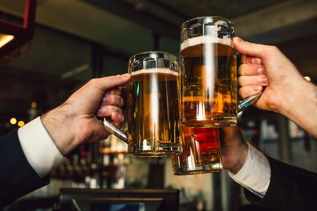 Cuadro de tres tazas de cerveza en manos de los hombres. la gente usa trajes. estan en el bar.