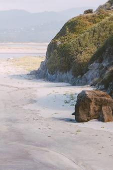 Cuadro vertical de rocas cubiertas de musgos con colinas y ríos.