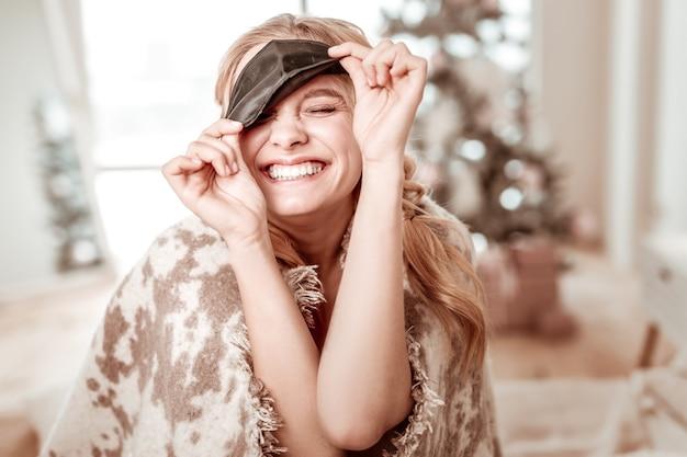 Con cuadros grises. mujer rubia muy alegre con máscara negra para dormir y mostrando su amplia sonrisa