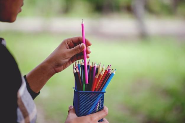 Cuadros de la mano y del lápiz, concepto de la educación del color de fondo verde con el espacio de la copia