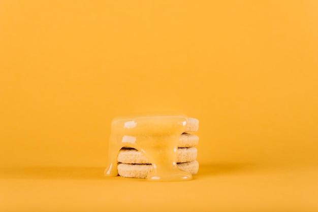 Cuajada de limón que gotea sobre la pila de galletas en el contexto amarillo