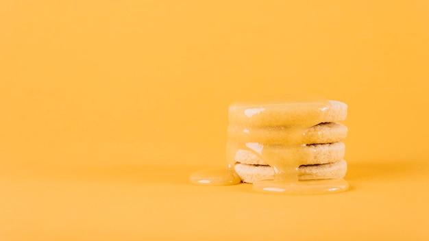 Cuajada de limón que gotea sobre la pila de galletas en fondo amarillo
