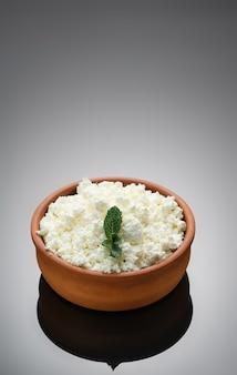 Cuajada en taza de cerámica rústica. primer plano, enfoque selectivo, fondo oscuro con espacio de copia. requesón, comida sana natural, comida de dieta completa