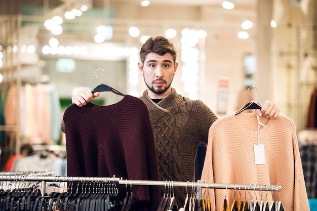 Cuál elegir el concepto de elección. un adolescente con dos suéteres junto a la barandilla en una tienda departamental.
