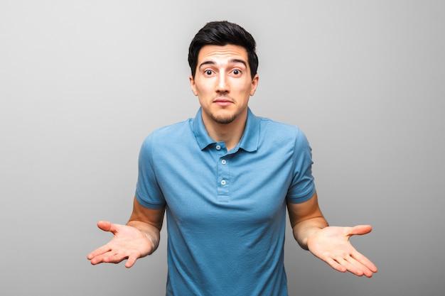 Cuál es el problema. pidiendo gesto de hombre guapo en camisa azul