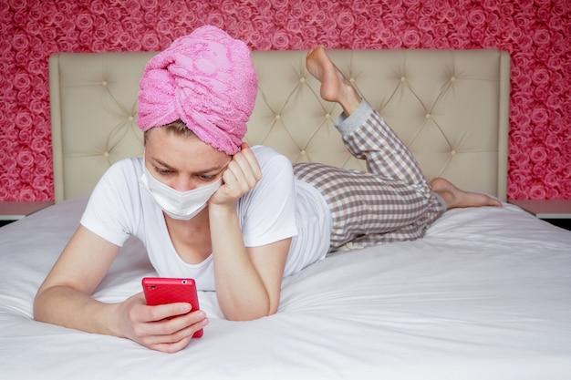 Cuarentena en casa. una joven bloguera caucásica con una máscara médica protectora y una toalla sobre su cabeza está acostada en la cama con un teléfono. recreación y hobbies. comunicación remota en mensajeros.