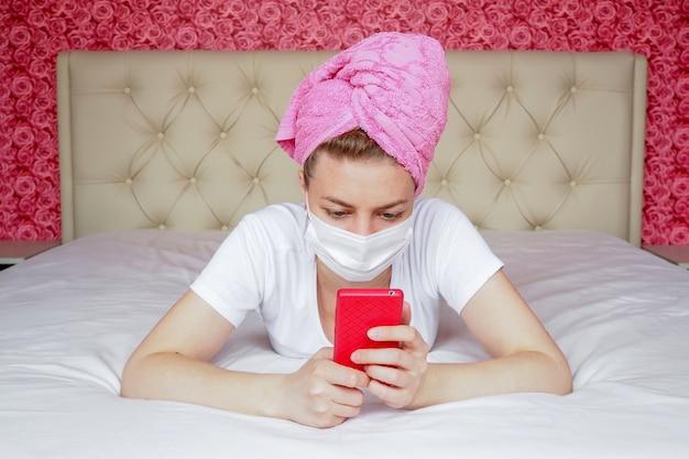 Cuarentena en casa. una joven bloguera caucásica con máscara y una toalla sobre su cabeza está acostada en la cama con un teléfono. comunicación remota en mensajeros.
