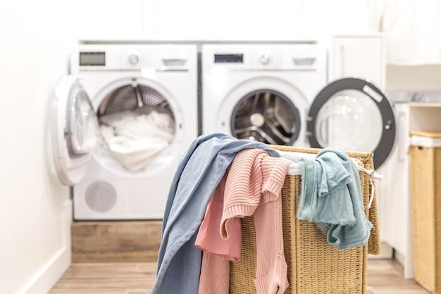 Cuarto de lavado con cesto y lavadoras y secadoras.