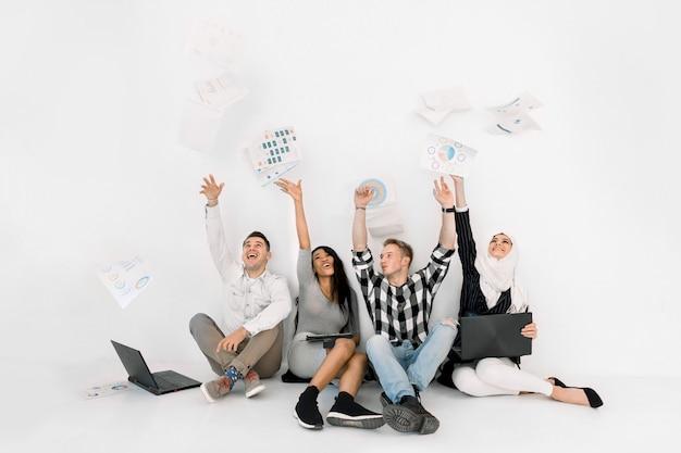 Cuatro alegres personas multiétnicas diferentes, niñas africanas y musulmanas y hombres caucásicos, vomitando papeles de trabajo, sentados en el suelo, aislados en blanco