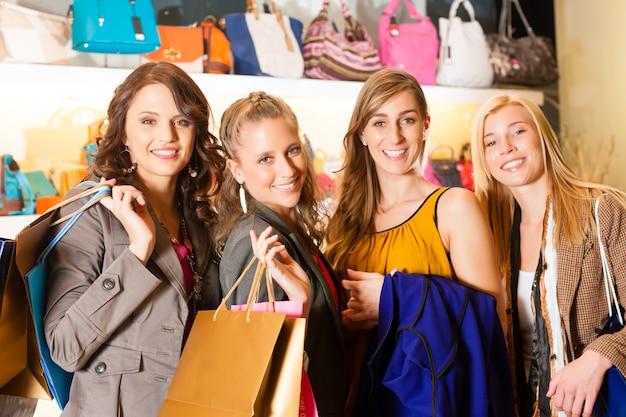 Cuatro amigas bolsas de compras en un centro comercial