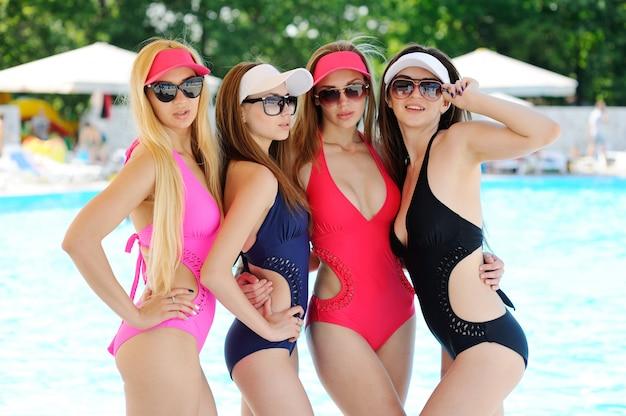 Cuatro amigas en trajes de baño cerrados de colores, gorras y gafas de sol