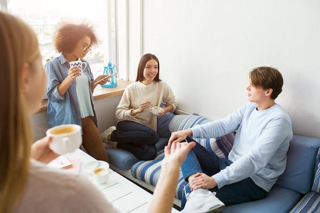 Cuatro amigos están reunidos. están hablando entre ellos y divirtiéndose.