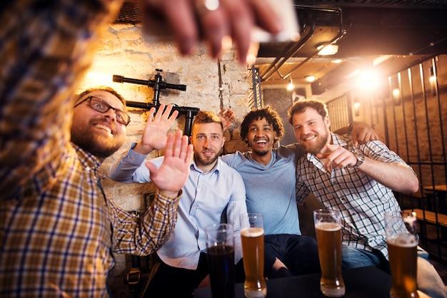Cuatro amigos multiculturales sonrientes saludando y tomando una selfie mientras está sentado en el pub.