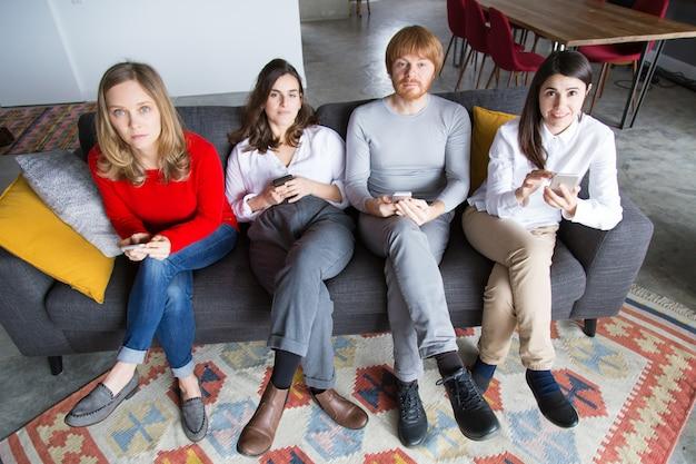 Cuatro amigos posando en el sofá con teléfonos inteligentes en las manos