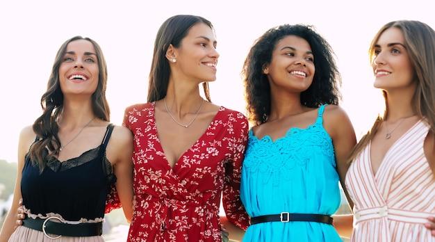 Cuatro atractivas mujeres posan en el fondo urbano, abrazándose la cintura, sonriendo ampliamente y disfrutando de su juventud.