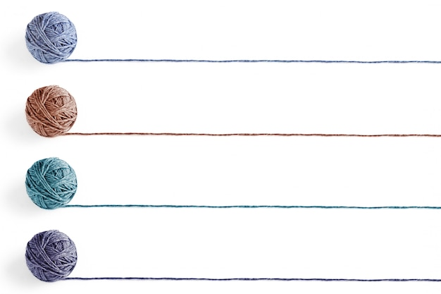 Cuatro bolas de lana multicolores de hilo aislado sobre fondo blanco. en blanco para la lista.