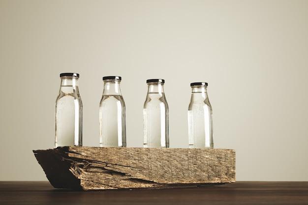 Cuatro botellas de vidrio transparente transparente con tapas negras llenas de agua potable pura presentadas en ladrillo de madera, aislado en blanco