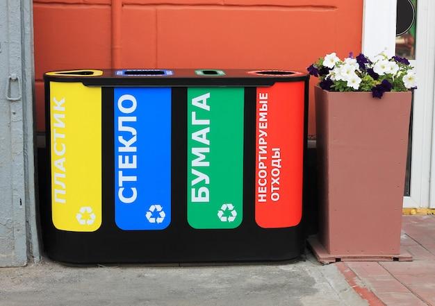 Cuatro botes de basura para la recogida selectiva de basura con la inscripción en ruso