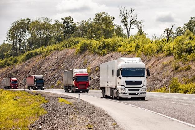 Cuatro camiones de diferentes colores moviéndose por una carretera.