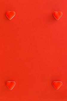 Cuatro caramelos en forma de corazón en la esquina de fondo rojo