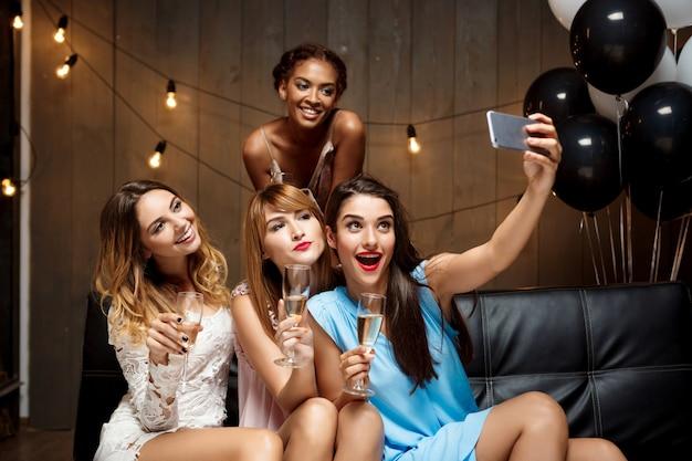 Cuatro chicas guapas haciendo selfie en fiesta.