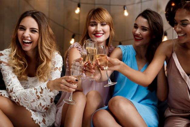 Cuatro chicas guapas tintineo de copas con champán en la fiesta.