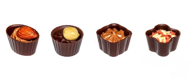 Cuatro chocolates con crema y nueces surtido de chocolate sobre fondo blanco aislado