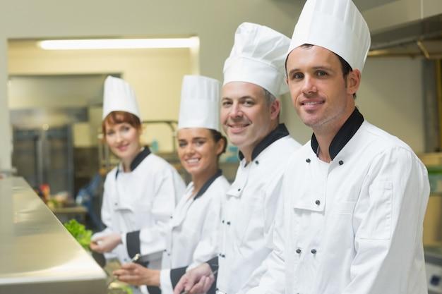 Cuatro cocineros trabajando en una cocina de pie en una fila.