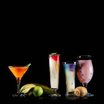 Cuatro cócteles y frutas exóticas sobre fondo negro