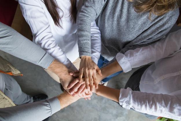 Cuatro colegas uniendo sus manos