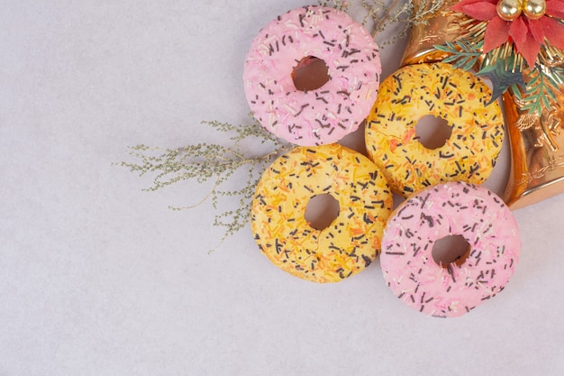 Cuatro coloridos donuts dulces sobre superficie blanca