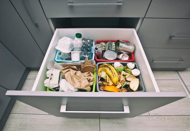Cuatro contenedores diferentes para clasificar la basura. para residuos plásticos, de papel, metálicos y orgánicos.