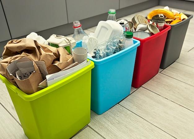 Los cuatro contenedores diferentes para clasificar la basura. para residuos plásticos, de papel, metálicos y orgánicos.