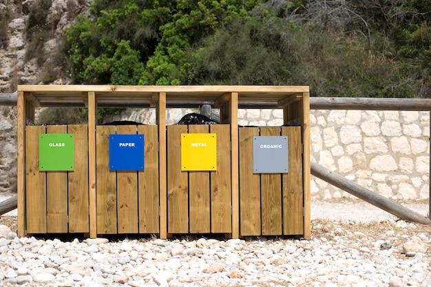 Cuatro contenedores de madera para diferentes basuras.