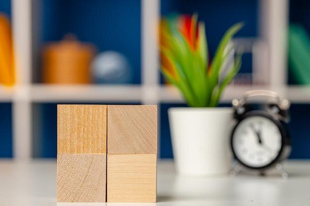 Cuatro cubos de madera con espacio de copia y despertador en el escritorio