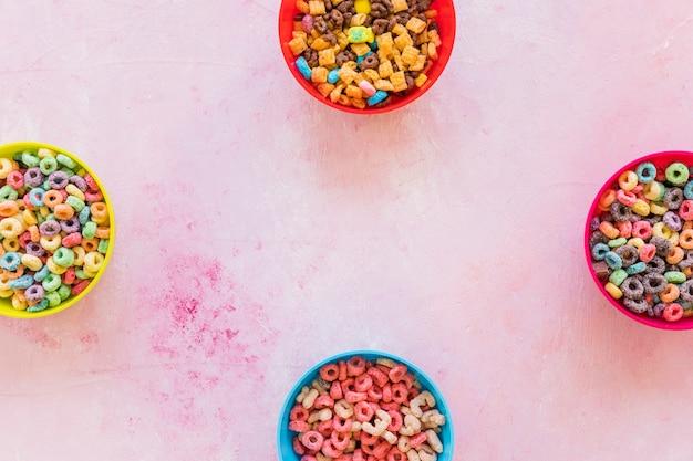 Cuatro cuencos con cereales en mesa rosa.