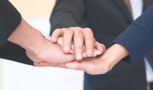 Cuatro de la mano juntos en la reunión de negocios para el concepto de equipo
