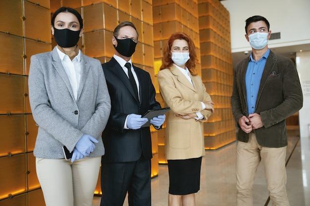 Cuatro elegantes compañeros de trabajo siguiendo las precauciones de seguridad.