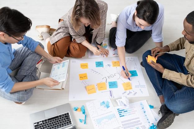 Cuatro emprendedores interculturales en ropa informal sentados en el piso de la oficina y preparándose para la conferencia mientras discuten nuevas ideas