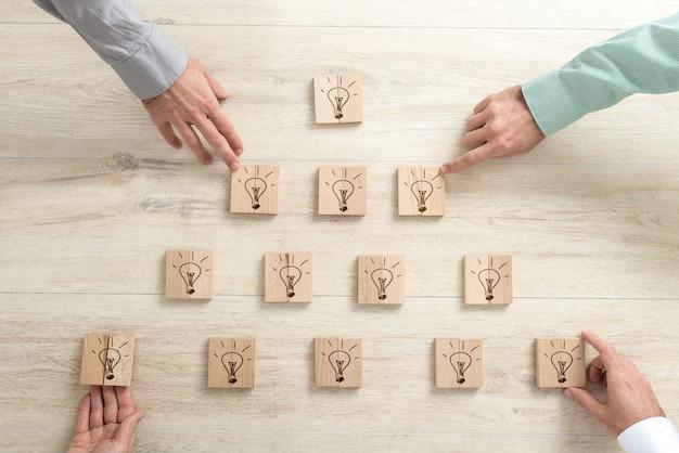Cuatro empresarios colocando bloques de madera con bombillas en forma de pirámide