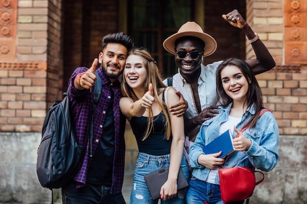 Cuatro estudiantes felices cerca de la universidad en el campus.