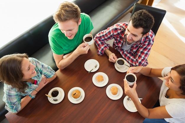 Cuatro estudiantes sonrientes tomando una taza de café