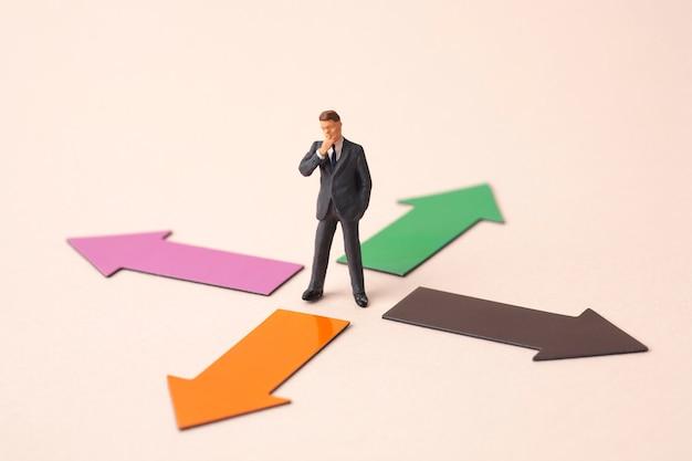 Cuatro flechas de dirección con hombre de negocios en miniatura