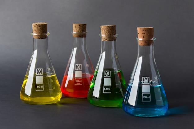 Cuatro frascos de laboratorio con tapones de corcho y líquidos coloridos aislados sobre fondo oscuro.
