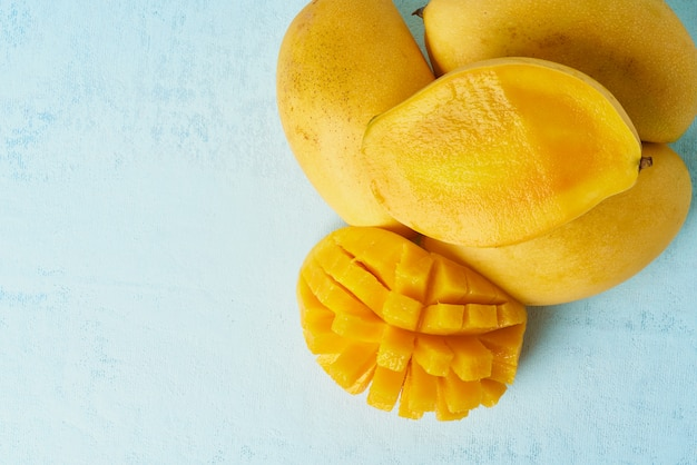 Cuatro frutas enteras de mango en una mesa azul brillante y cortadas en rodajas. grandes frutas amarillas jugosas