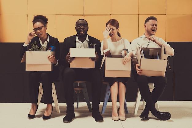 Cuatro gerentes despedidos sentados con cajas de oficina