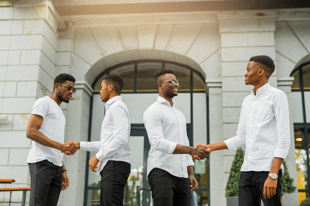 Cuatro guapos jóvenes africanos con camisas blancas.