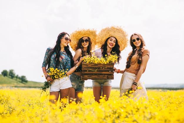 Cuatro hermosa chica hippie en un campo de flores amarillas.