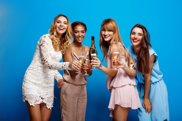 Cuatro hermosas chicas descansando en la fiesta sobre la pared azul